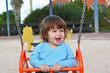 The beautiful little boy laughs  at a red swing