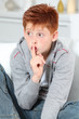 Young boy with finger on his mounth