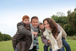 Parents doing piggyback to their children in countryside