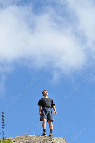 A young man stands on a cliff top, and seriously,