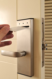 A hand inserting keycard in the electronic lock. poster