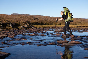 female hiker is crossing the river