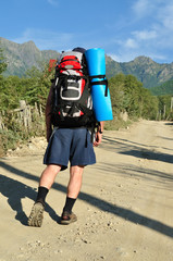 Tourist with a large backpack is a high mountain, on the road