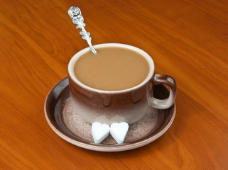 Cup of coffee with sugar cube shaped as heart