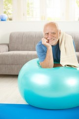 Portrait of sporty senior man with exercise ball