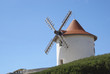 White windmill against blue sky located in Corsica