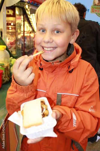 Ein kleiner Junge isst frische gebackene Champignons