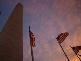 flags moving in front of the washington monument during sunset