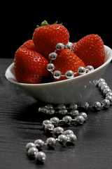 white fruit dish filled with red strawberries decorated with sil