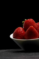 white fruit dish filled with red strawberries