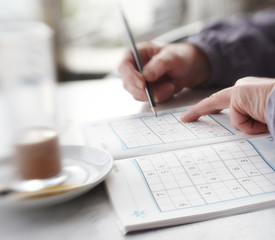 Woman trying to solve Sudoku Puzzle