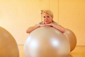 Frau in Turnhalle mit Gymnastikbal