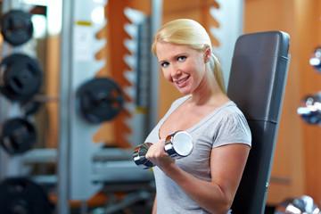 Frau mit Hantel im Fitnessstudio