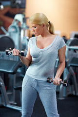 Frau trainiert mit zwei Hanteln