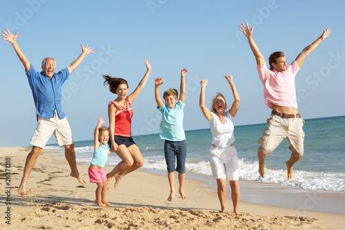 Portrait Of Three Generation Family On Beach Holiday Jumping In