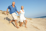 Senior Couple Enjoying Beach Holiday Running Down Dune