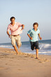 Father And Son Running Along Summer Beach