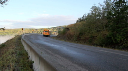 school bus climbing hill and going around a corner