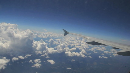 Aerial view of airplane wing tilt over clouds