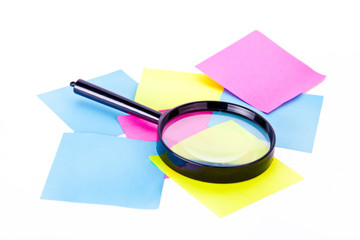 Notes and loupe isolated at white background.