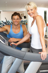 Senior Woman Working With Personal Trainer On Running Machine In