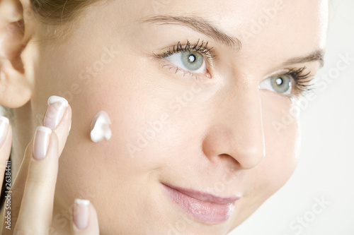 portrait of woman putting cream on face