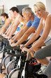 Senior Woman Cycling In Spinning Class In Gym