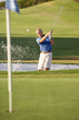 Senior Male Golfer Playing Bunker Shot On Golf Course