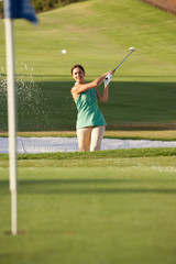 Female Golfer Playing Bunker Shot On Golf Course