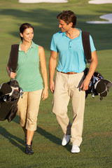 Couple Walking Along Golf Course Carrying Bags