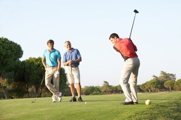 Group Of Male Golfers Teeing Off On Golf Course