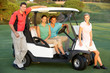 Group Of Friends Riding In Golf Buggy On Golf Course