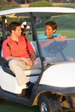 Two Male Golfers Riding In Golf Buggy On Golf Course