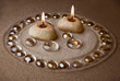 Candles and glass drops on sand. Sepia tinted, vintage imitating
