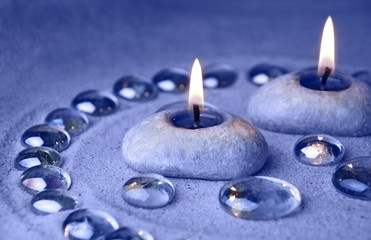 Candles and glass drops on sand. Blue tinted