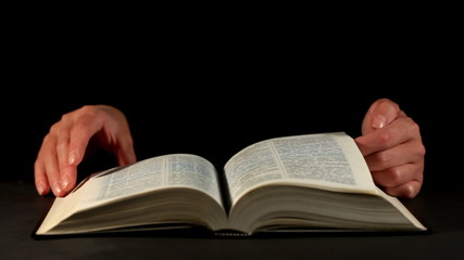 Hands and book over dark background