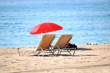chaise lounge and umbrella on a beach of mediterranean sea in ba