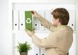 Man drawing out green folder
