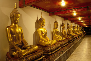 Buddha images in Thai temple at night in ambient golden lights