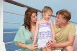 Happy parents with small daughter enjoy sea on yacht