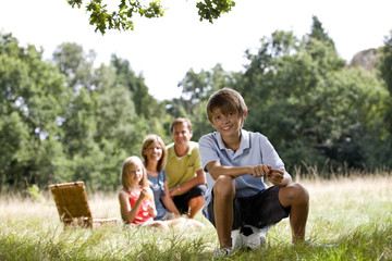 A family having a picnic, young boy sitting on a football