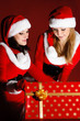 two woman in Santa costume opening christmas gift