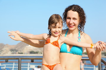 smiling woman with her daughter on deck of cruise ship.