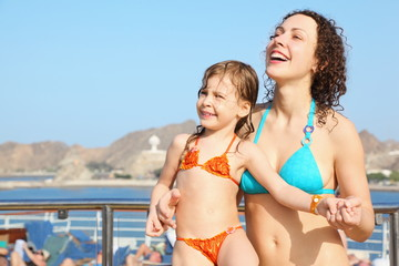 smiling woman with daughter is standing on deck of cruise ship