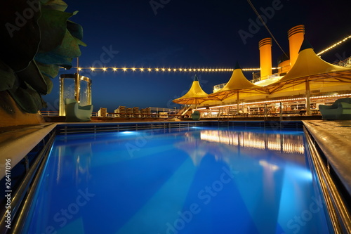 illuminated deck of ship at evening. swimming pool in center