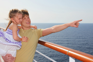 father standing on cruise liner deck, carrying his daughter and