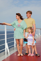 family with daughter standing on cruise liner deck, full body