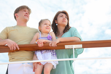 family with daughter standing on cruise liner deck near rail