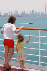 mother and daughter standing near rail on cruise liner deck