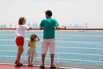 family with daughter standing on cruise liner deck